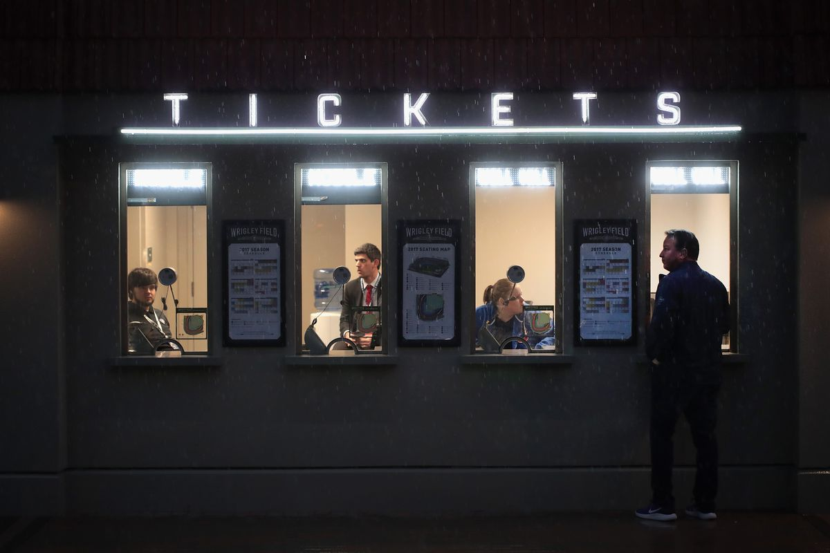 CHICAGO, IL - APRIL 10:  A fan stands at the ticket window in the rain outside of Wrigley Field before the start of the 2017 home opener against the Los Angeles Dodgers on April 10, 2017 in Chicago, Illinois. The Cubs defeated the Cleveland Indians in seven games to win the 2016 World Series.  (Photo by Scott Olson/Getty Images)