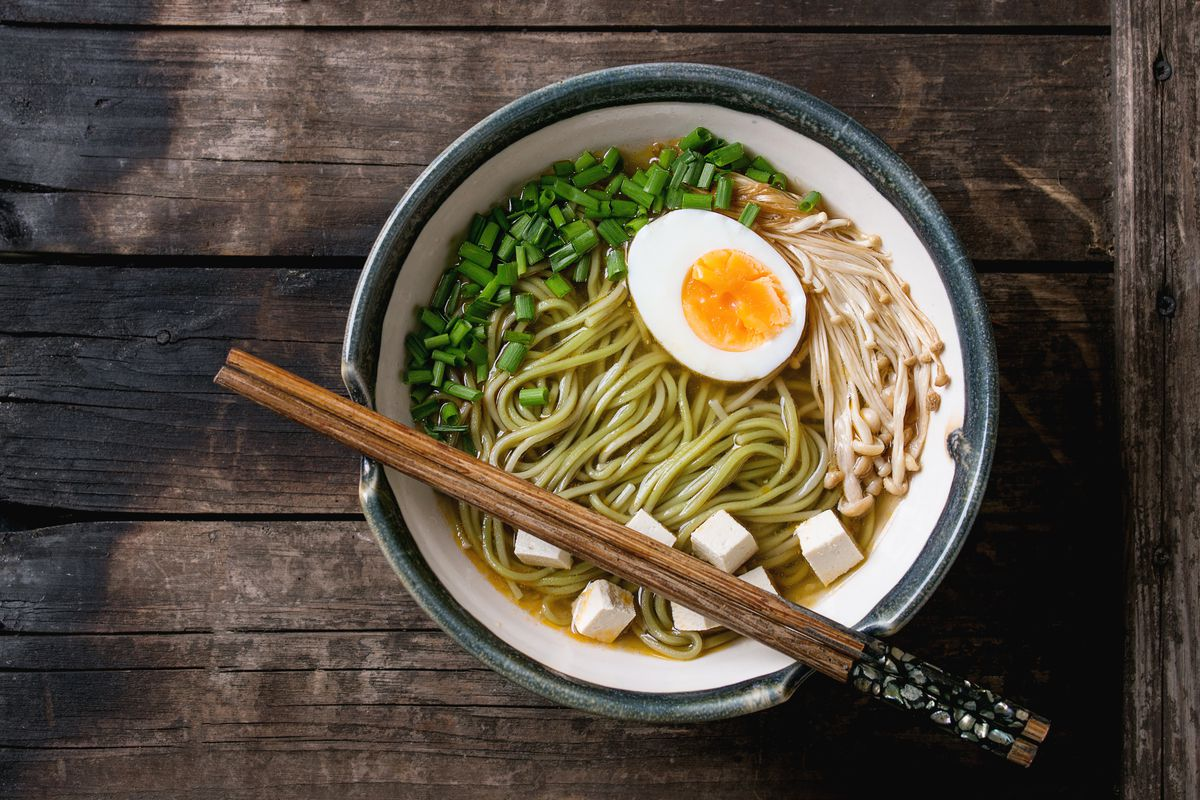 Ceramic bowl of asian style soup with green tea soba noodles, egg, mushrooms, spring onion and tofu cheese, served with chopsticks over old wooden background. Top view, copy space