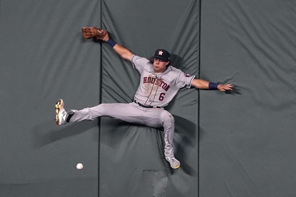 Jake Meyers #6 of the Houston Astros collides with the wall as he attempts to catch a ball hit by Carlos Santana of the Kansas City Royals in the fifth inning at Kauffman Stadium on August 16, 2021 in Kansas City, Missouri.