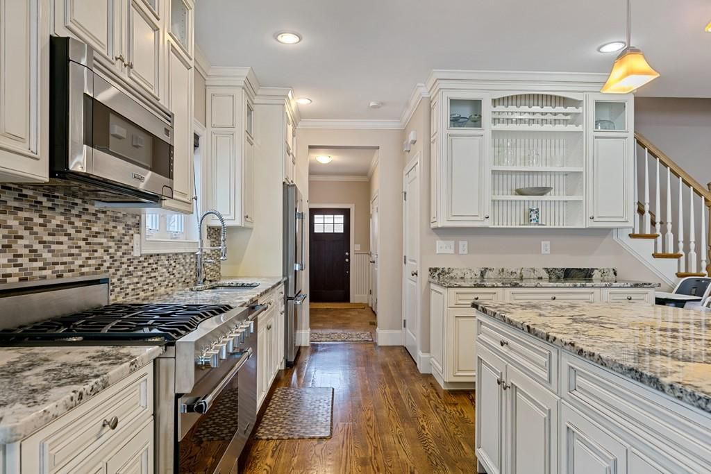 A kitchen with an island and a long counter with a stove.