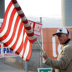 Jim Matheson supporter Clint Warby rolls up an American flag after a honk and wave at 13400 South and Bangerter Highway in Riverton on Friday, Nov. 2, 2012.