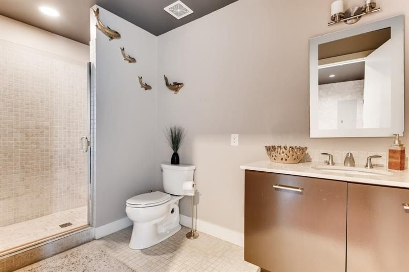 A white and tiled bathroom with small fish sculptures on the walls.