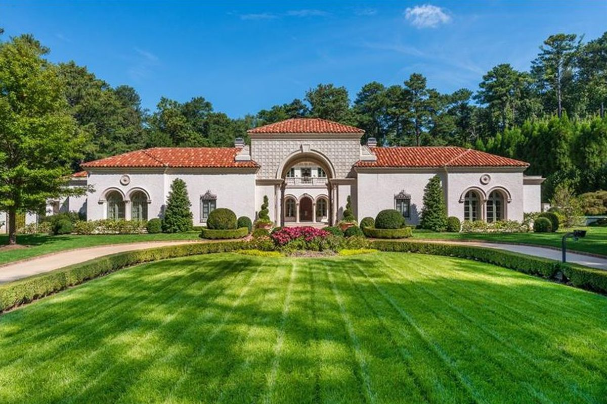 Front lawn leads up to Mediterranean mansion.