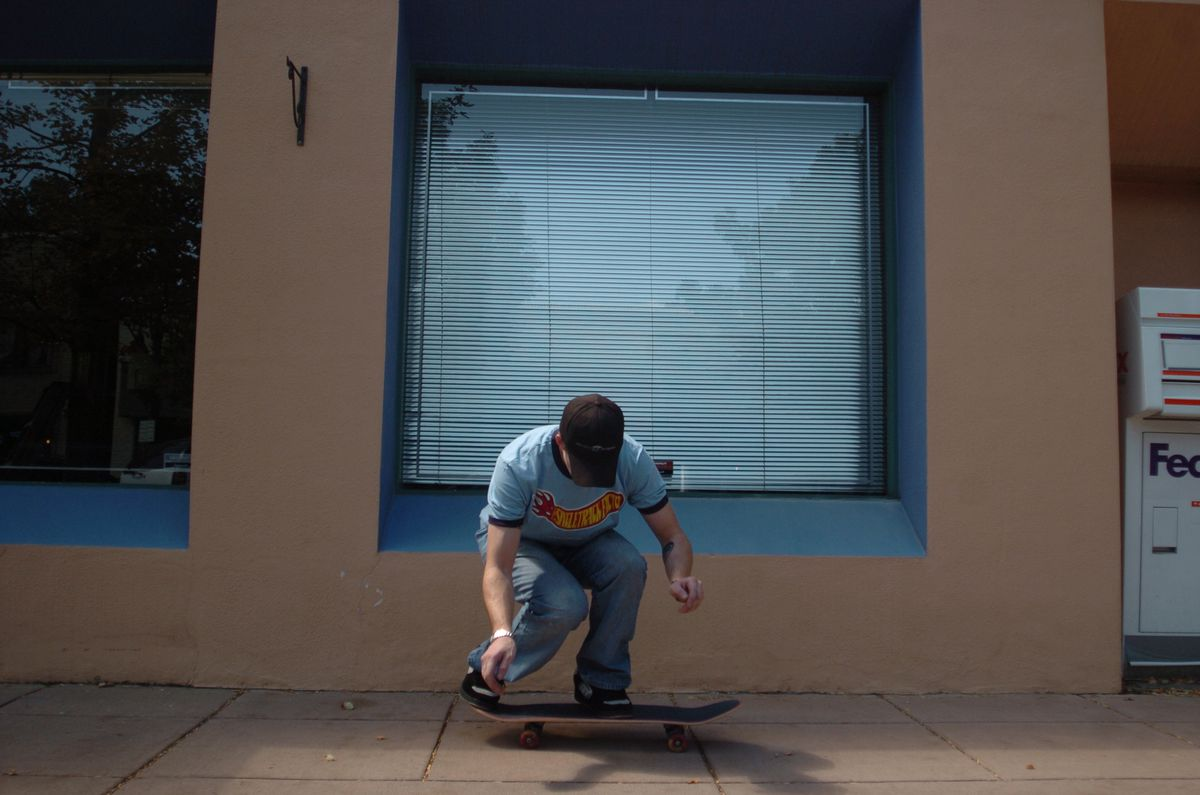 a skateboarder rides down the street bending his knees preparing to jump