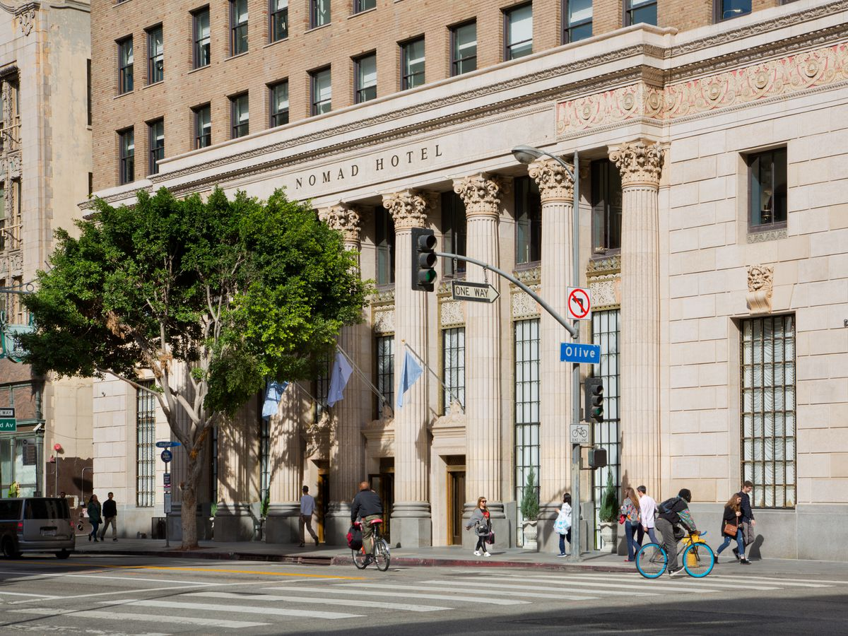 The exterior of the Bank of Italy building in Los Angeles. The facade is tan with columns on the front of the building.