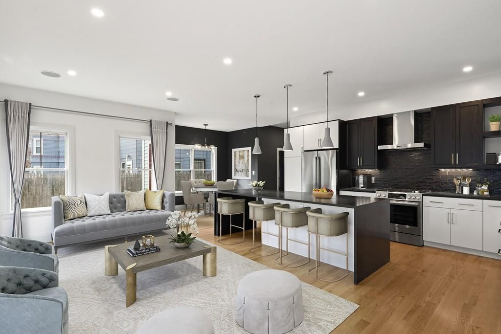 An airy, open living room-kitchen area with an island separating the two rooms.