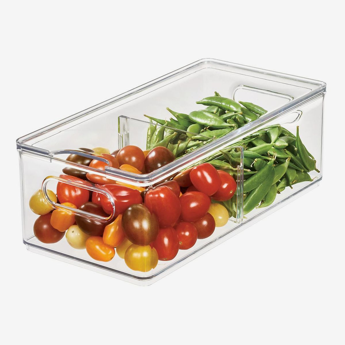 A clear storage bin with a divider containing tomatoes and snap peas