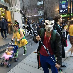 A Casey Jones (Teenage Mutant Ninja Turtles) cosplayer with a stick signed by hockey players.
