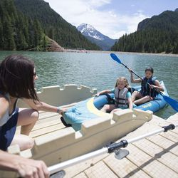 Sacha Gomez, left, pushes Courtney Clason, 10, and Lexi Gomez, 17, into the water from the floating dock on a sunny day at Tibble Fork Reservoir on Thursday, June 15, 2017.