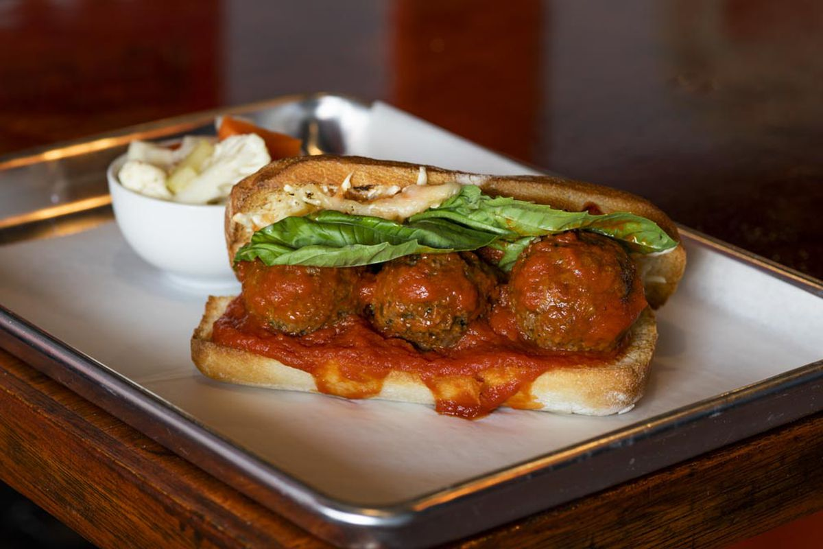 A trio of meatballs in red sauce sit on a long ciabatta bun.