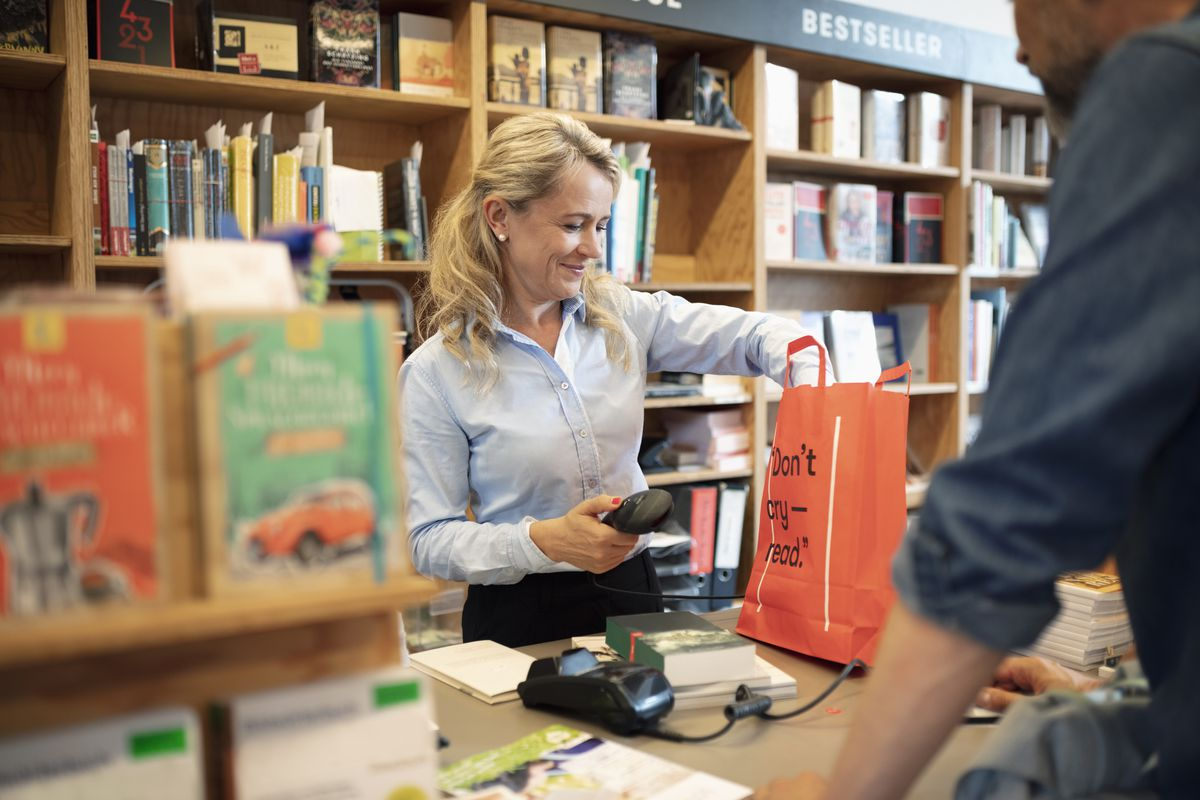 A clerk behind the counter in a bookstore puts a customer's purchases in a shopping bag.