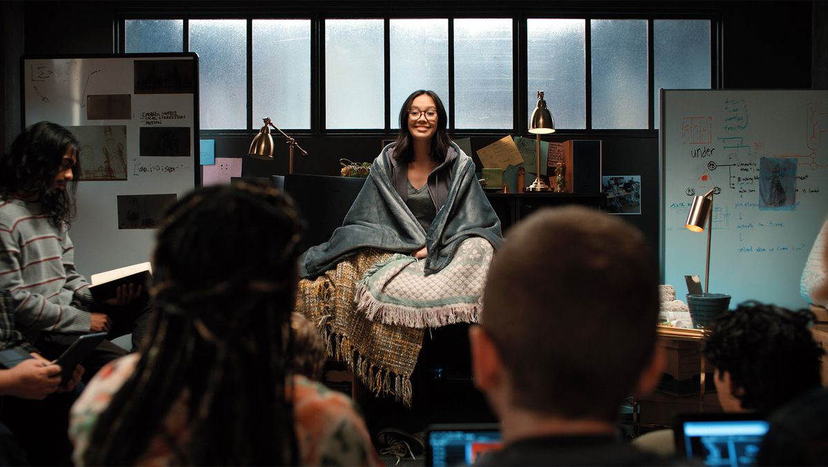 Charlotte Nicdao as Poppy Li sits wrapped in a blanket in the office in Mythic Quest, with her programming team around her