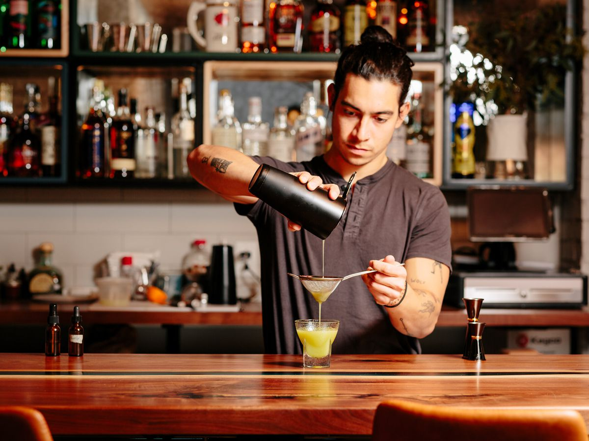 man behind a bar, pouring a green drink through a small sieve into a glass with ice in it