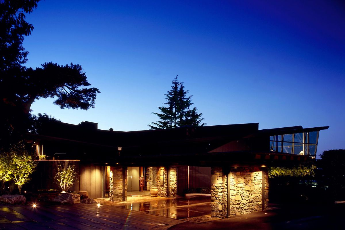 The exterior of Seattle's Canlis restaurant at twilight, with a large tree in the background and the front entrance illuminated
