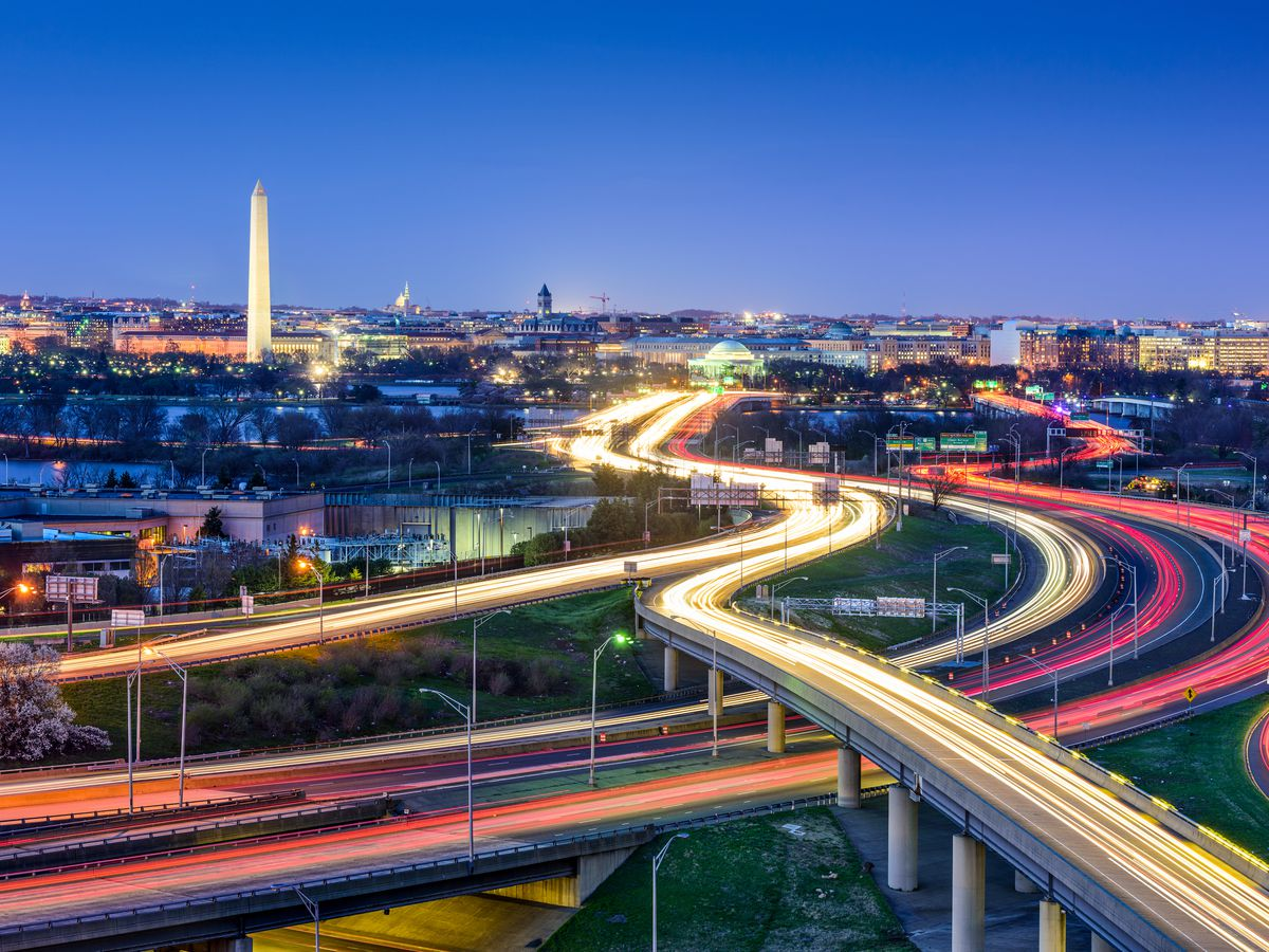 An aerial view of the cityscape of Washington D.C.. There are various highways in the foreground with the lights of the cars illuminating the roads. The Washington Monument is in the distance. It is evening.