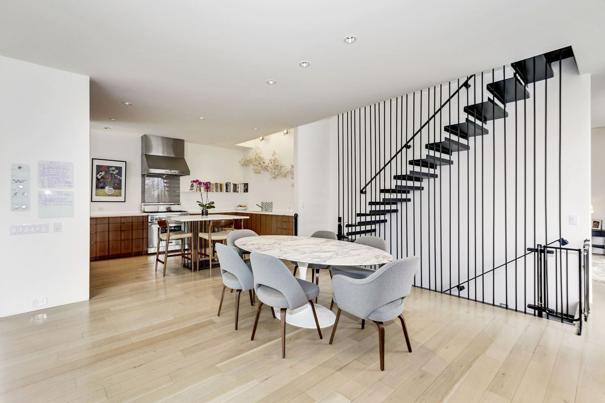 A white table with gray dining chairs sits next to a black steel floating staircase.