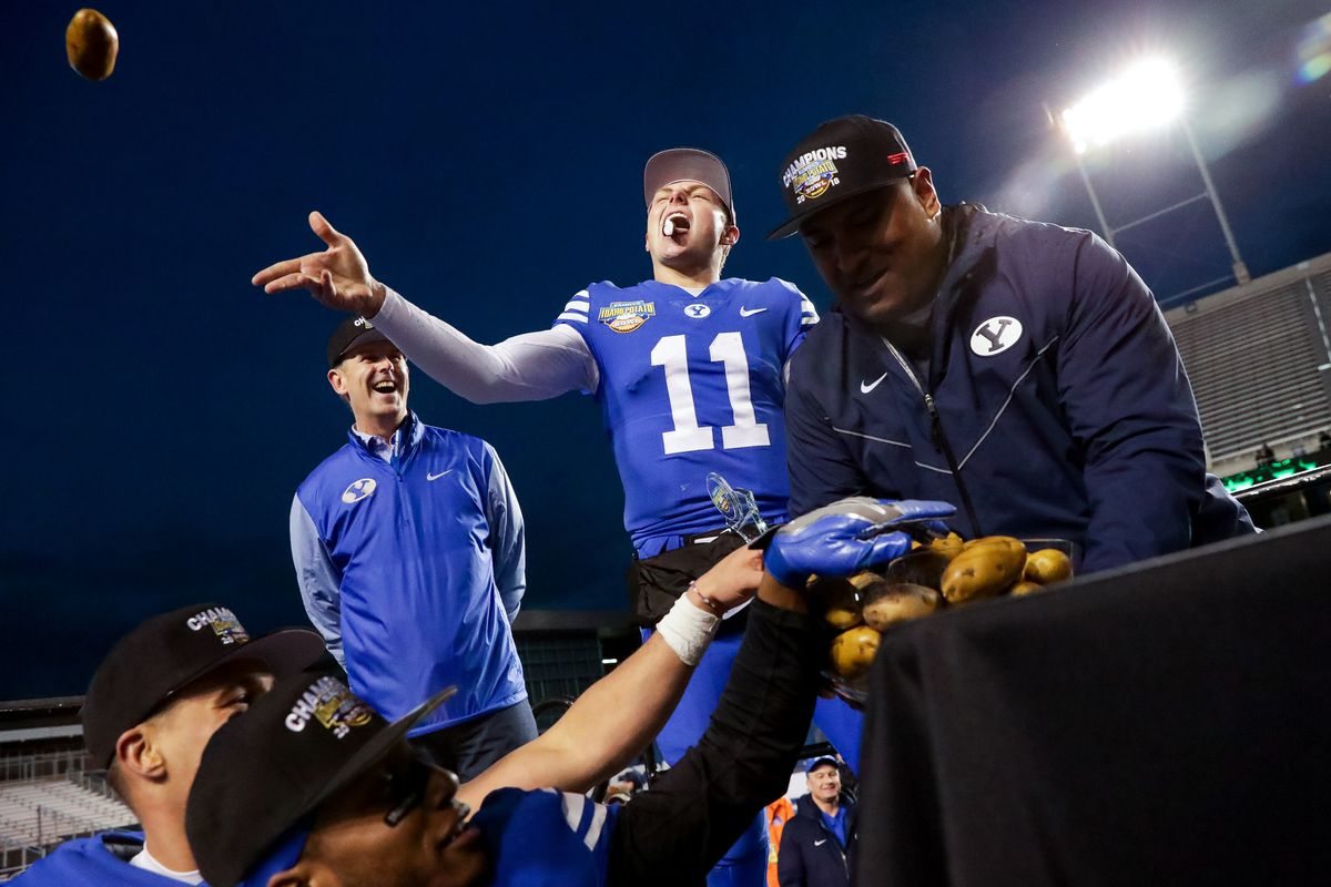Brigham Young Cougars head coach Kalani Sitake hands out the bowl trophy, full of fake potatoes, as quarterback Zach Wilson (11) takes a bite out of one, after their win over the Western Michigan Broncos in the Famous Idaho Potato Bowl at Albertsons Stadium in Boise, Idaho on Friday, Dec. 21, 2018.