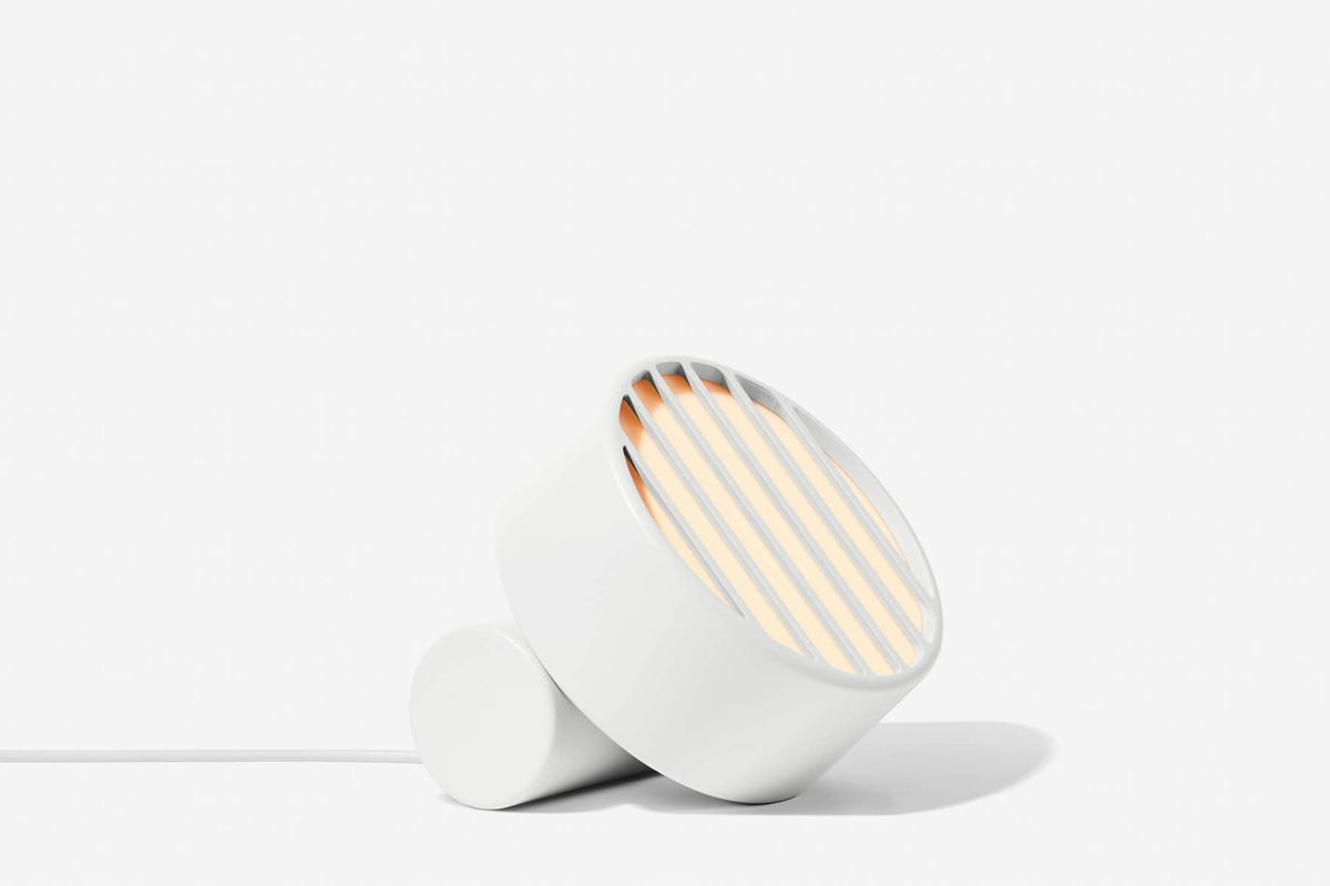 Flat round white lamp attached to a white cylindrical base.
