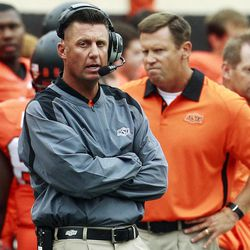 Oklahoma State head coach Mike Gundy talks on his headset as he watches from the sidelines in the fourth quarter of an NCAA college football game against Louisiana-Lafayette in Stillwater, Okla., Saturday, Sept. 15, 2012. Oklahoma State won 65-24.