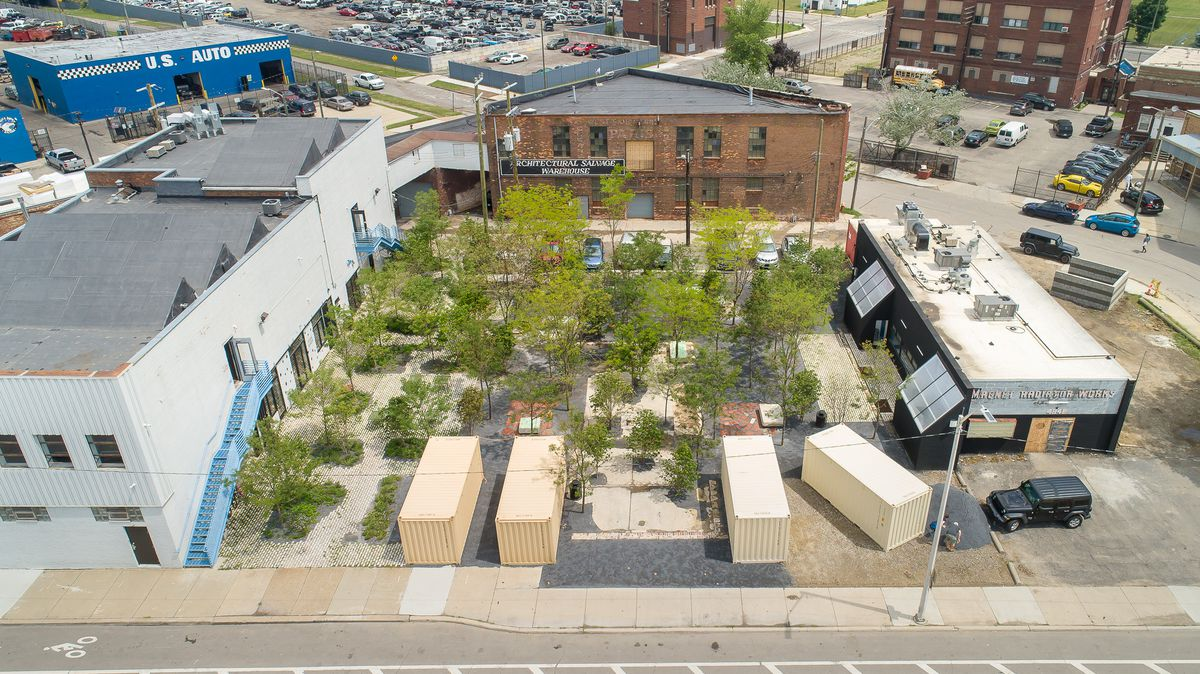 Aerial view of a plaza with trees. It's surrounded by three buildings and shipping containers.