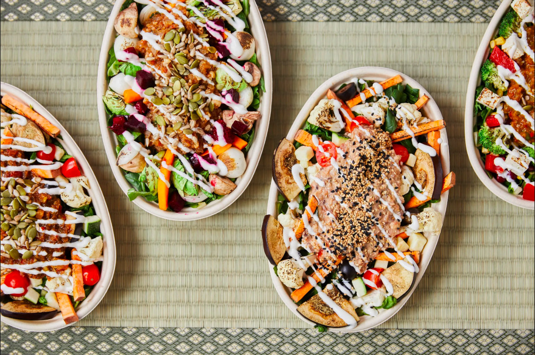 Overhead view of four vegetable bowls, each topped with a squiggle of white sauce, on a straw placemat