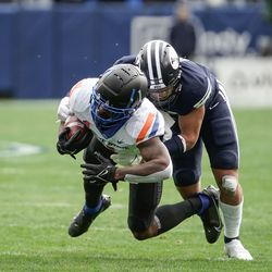 Boise State wide receiver Octavius Evans gets tackled by BYU safety Chaz Ah You during an NCAA college football game at LaVell Edwards Stadium in Provo on Saturday, Oct. 9, 2021.