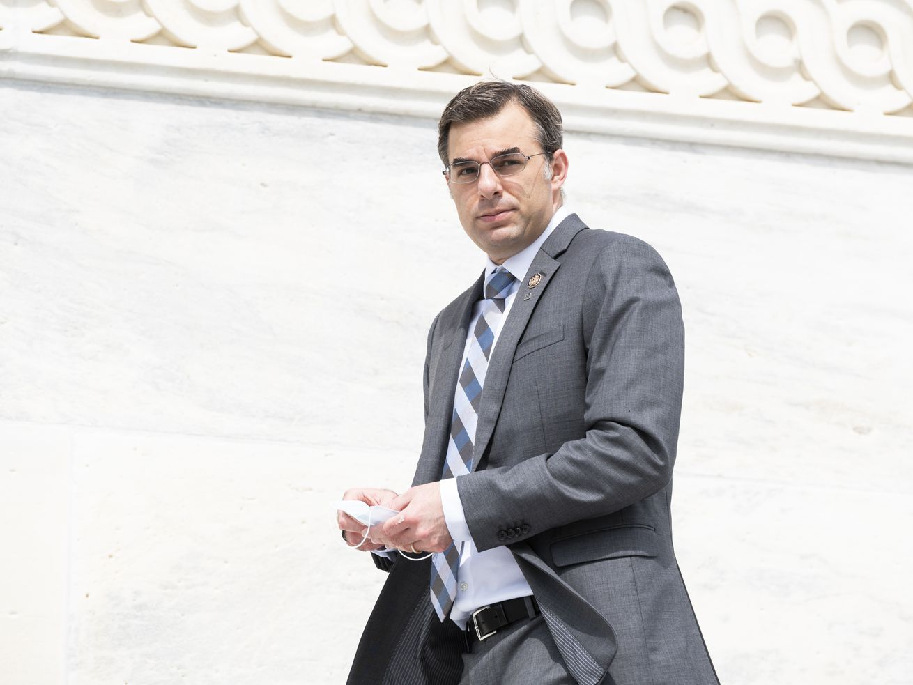 Amash, in a gray suit and gray-and-blue striped tie, holds a surgical mask as he walks.