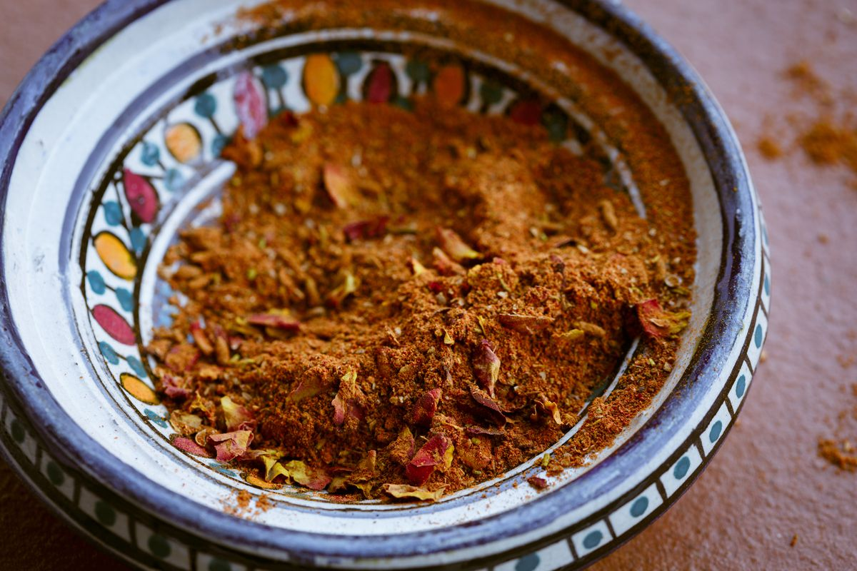 A painted clay bowl holds ras el hanout, an orange-brown blend of spices often used in Moroccan and other North African cooking.