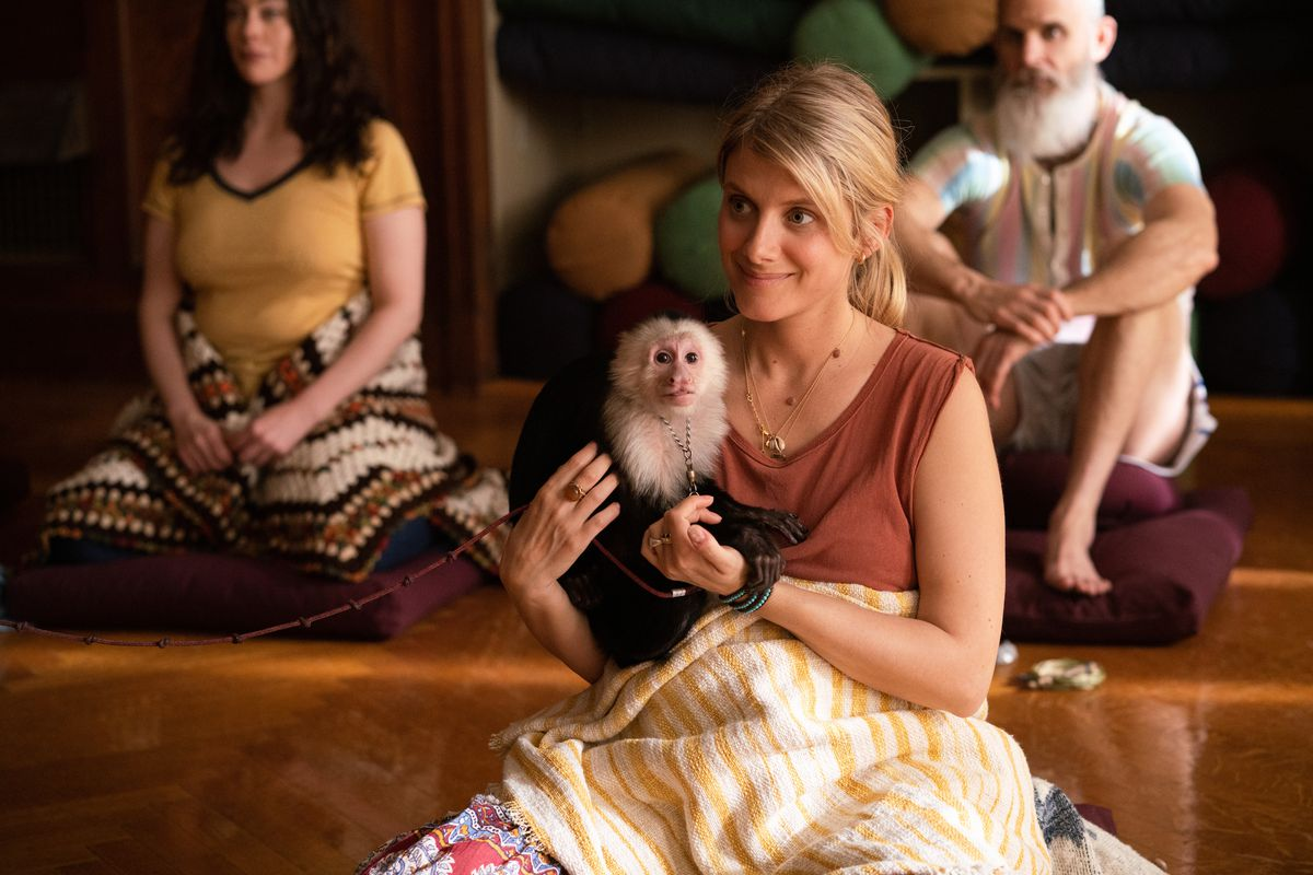 a sitting white woman in an orange top holds a capuchin monkey in Little America