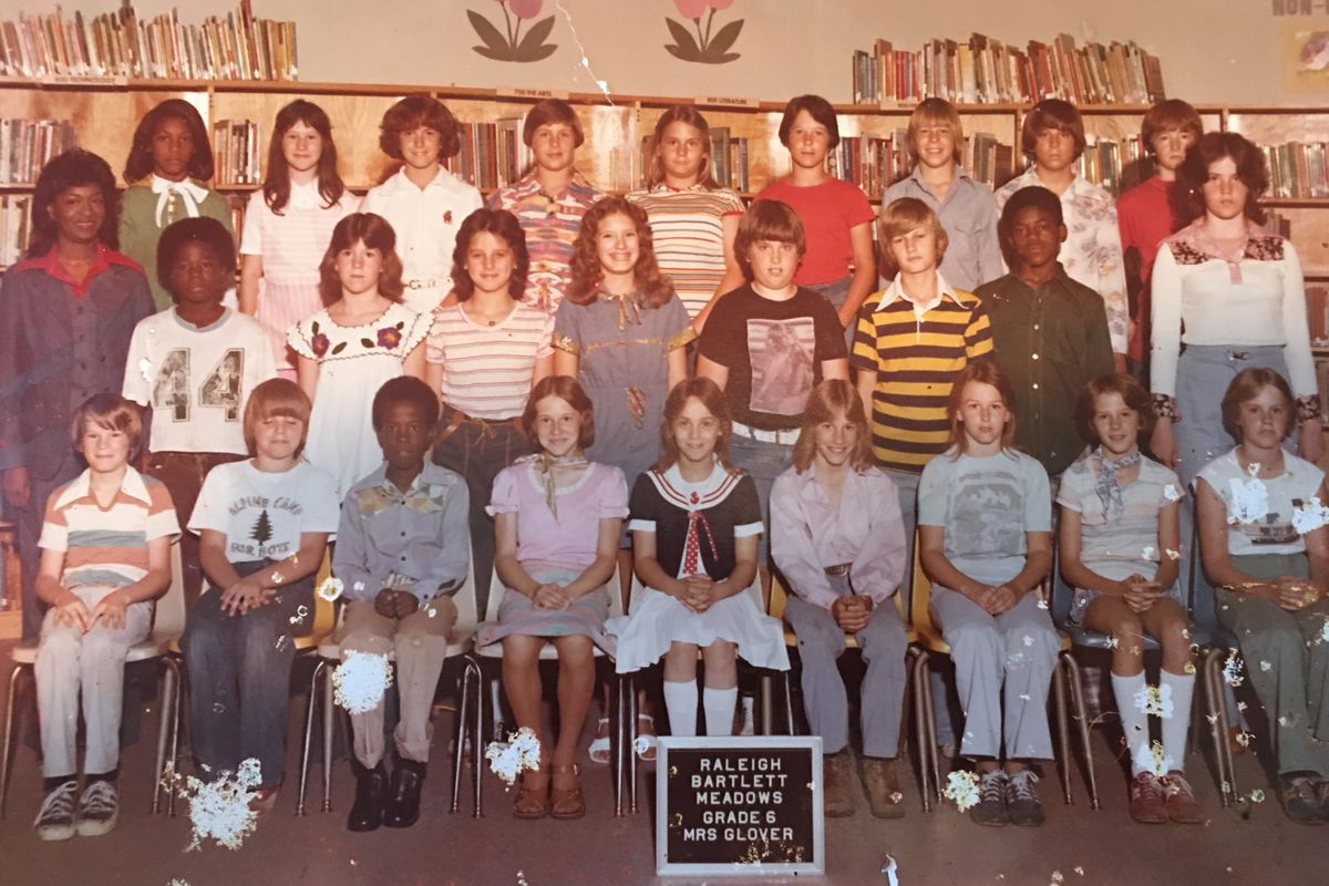 The integrated sixth grade class at Raleigh Bartlett-Meadows in the mid-1970s. Jacqueline Hill-Ferby, who was bused to the school from her home 45 minutes away, is standing on the far left, wearing green, behind one of her first professional role models and teacher, Mrs. Glover. Hill-Ferby, who became a teacher herself, says busing was a positive experience for her.