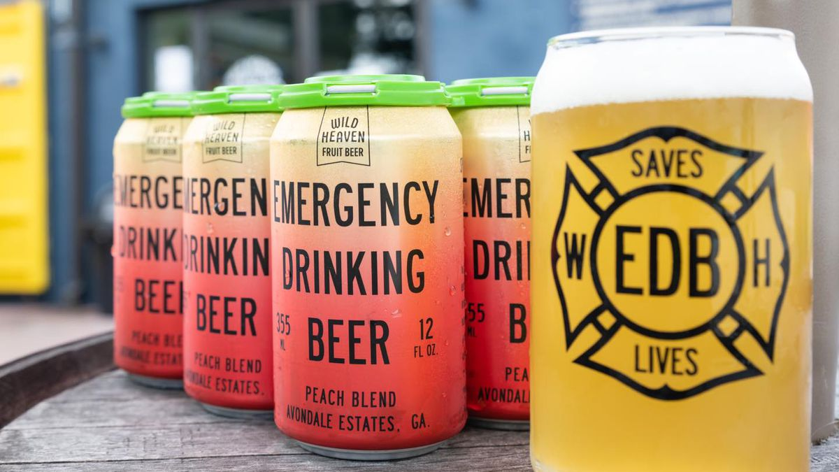 A six pack of peach and green colored cans of Emergency Drinking Beer peach blend next to a pink of the beer from Wild Heaven Beer in Avondale Estates, GA