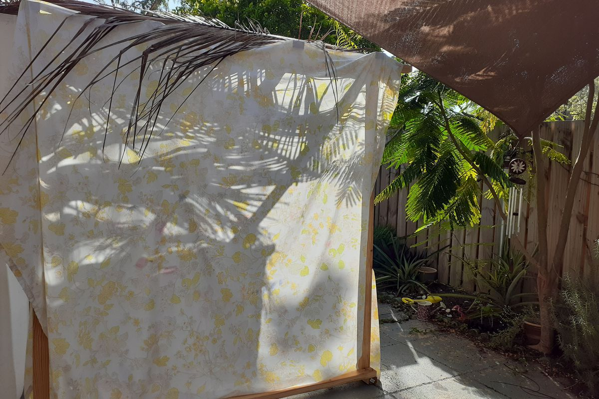 Mya Jaradat's sukkah, a temporary structure built by Jews to commemorate Shukkot, as viewed from the outside on Sept. 25, 2021, next to a flamboyant tree that is growing in the garden and that the Jaradet's daughter planted from a seed last year, during lockdown.