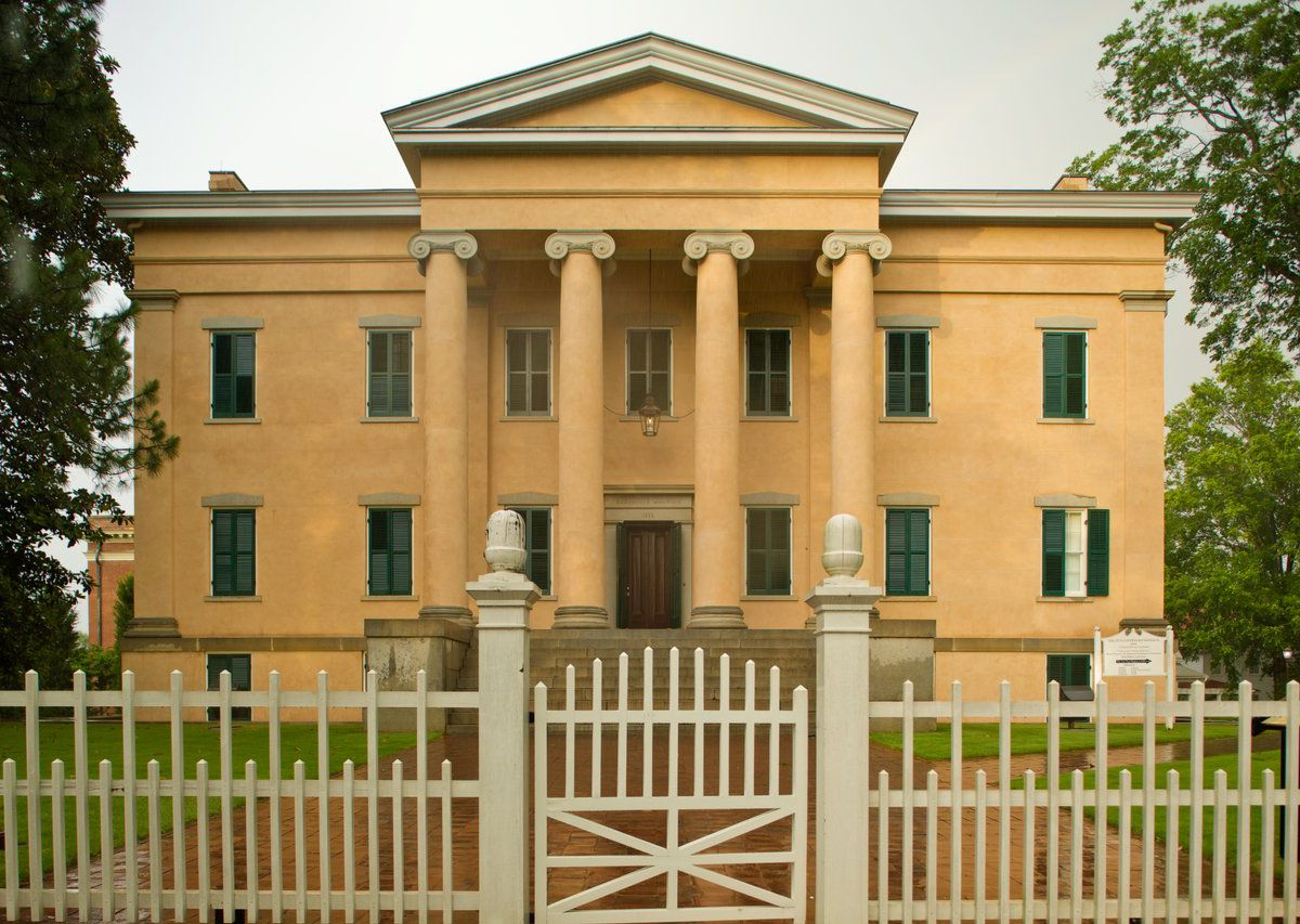 Beige-colored, three-story building with columns and an off-white fence in front.
