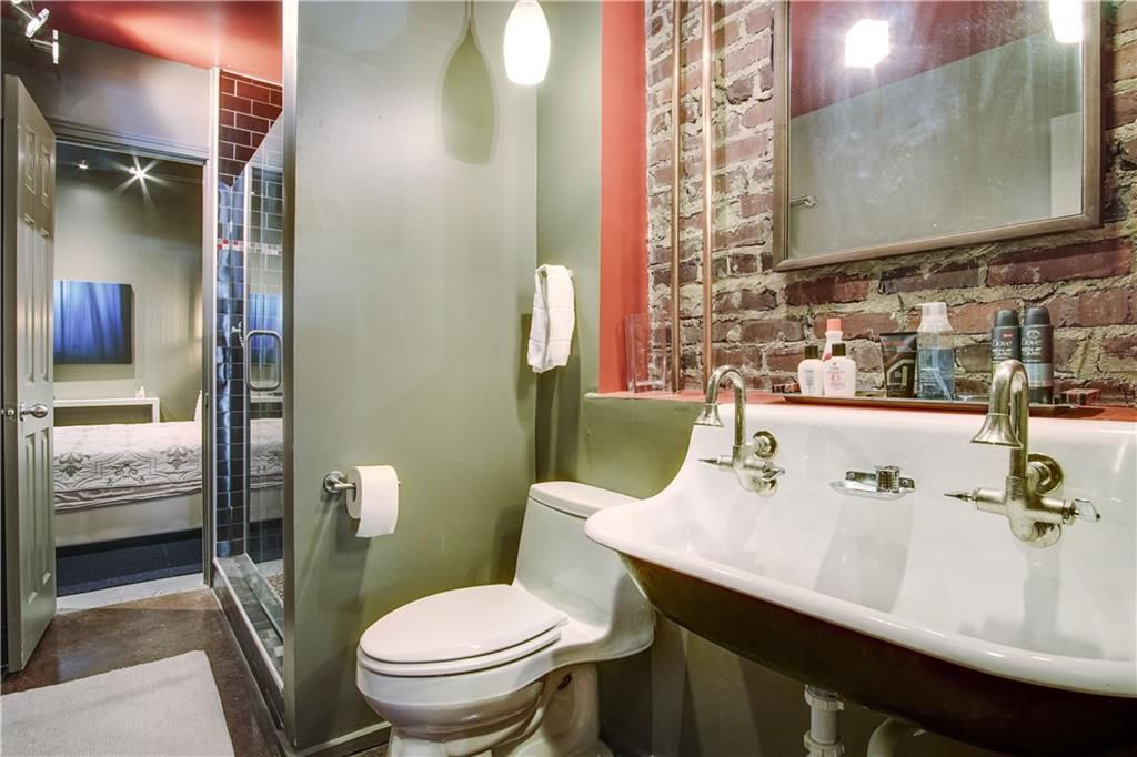 An old bathroom with new shower and old brick on the walls.