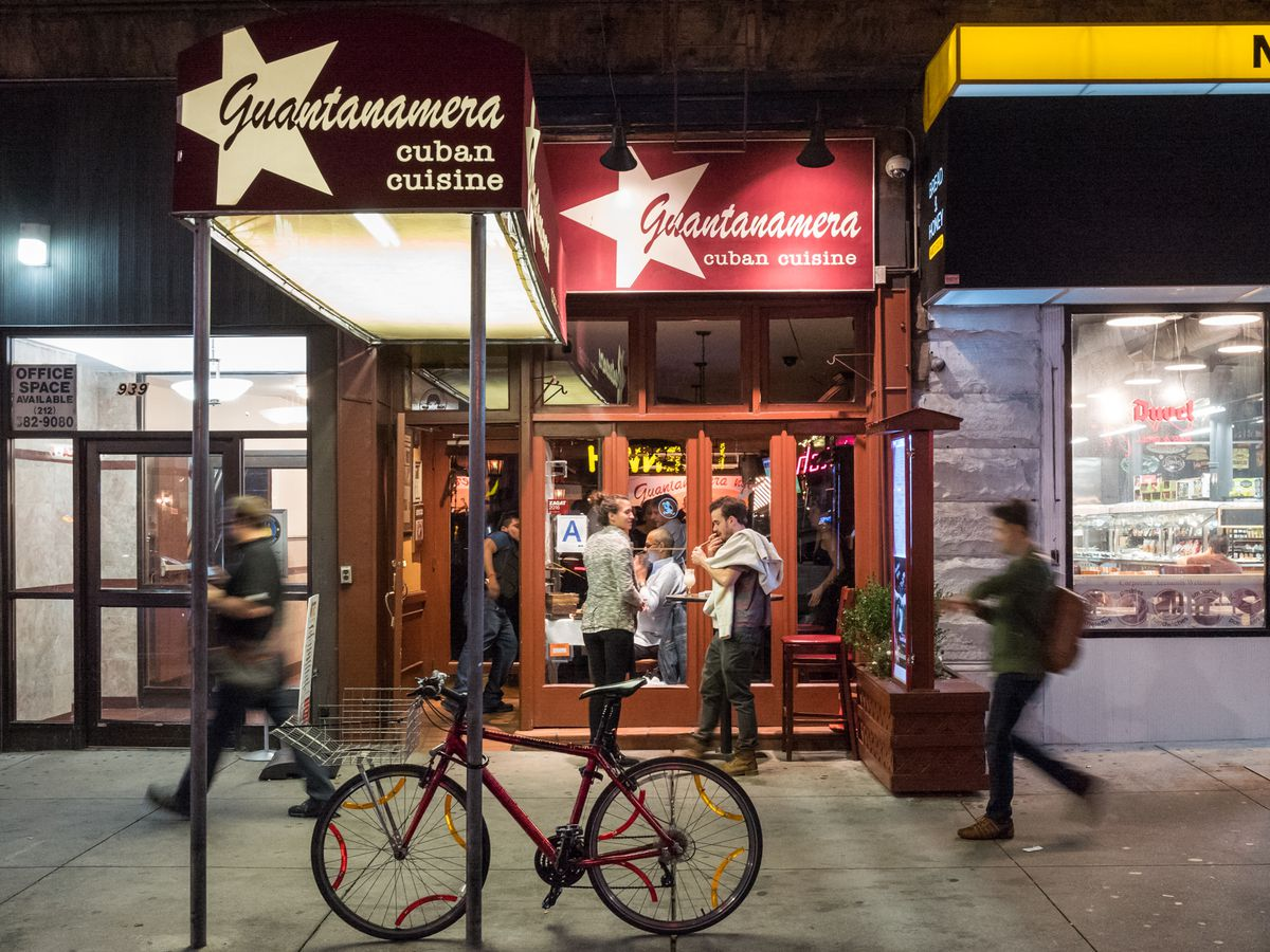 """People walk by the front of a restaurant with a red anwing that reads """"Guantanamera cuban cuisine"""" at night"""