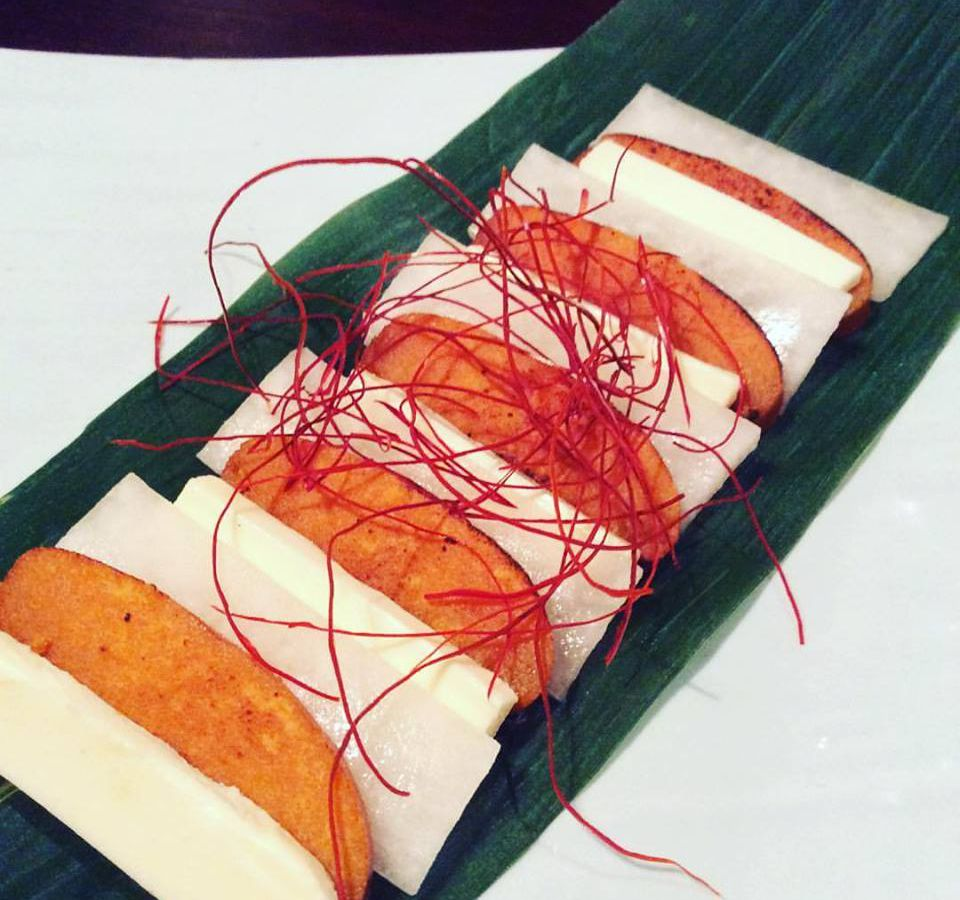 Mullet roe, miso cream cheese with daikon radish on a rectangular plate.