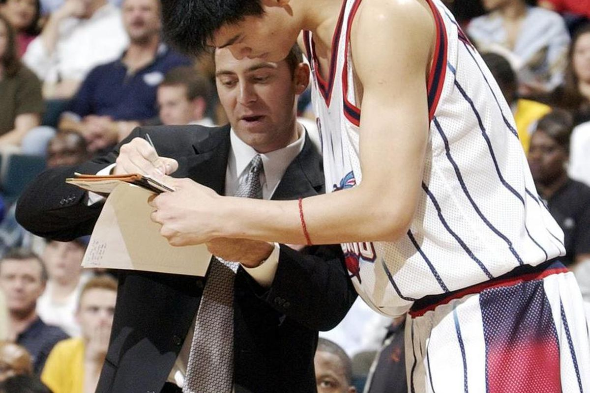 Houston Rockets assistant coach Mike Wells goes over a play with Yao Ming during a preseason game against the Philadelphia 76ers on Thursday, Oct. 24, 2002, in Houston. The 76ers beat the Rockets 93-89. (AP Photo/David J. Phillip)