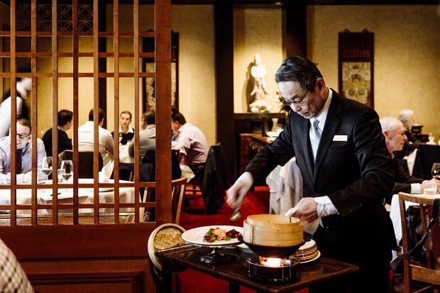 A waiter serves a dish tableside at Flower Drum