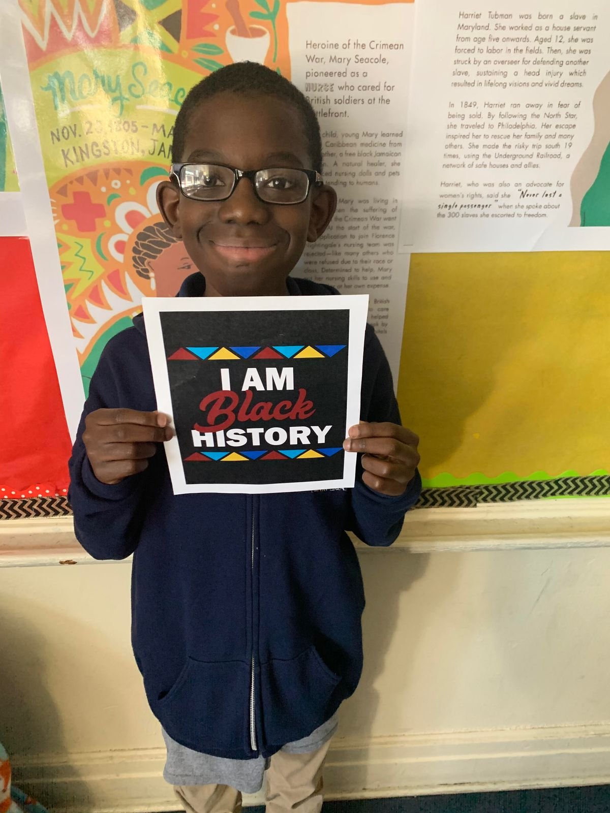 """Abdul Haq-Adome, a sixth-grade student smiling and holding a sign that reads """"I am Black history."""""""