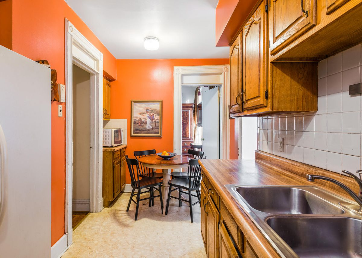 A kitchen with wood cabinetry, white tiles, and bright orange walls.