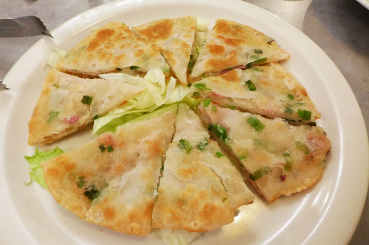 A round pancake cut into eight pieces flecked with green scallions.