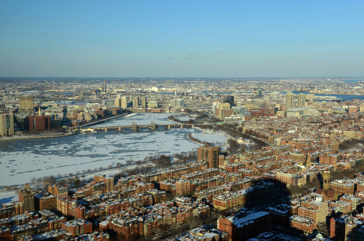 Aerial shot of two dense cities separated by a frozen river.