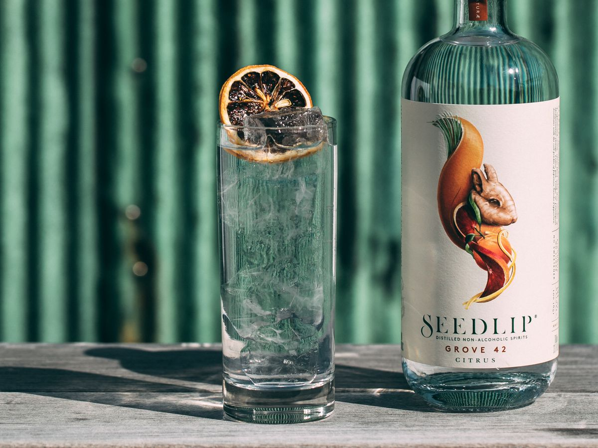 A non-alcoholic cocktail with tonic and topped with a dried blood orange on a bar at o ya restaurant in Manhattan. A bottle of Seedlip, a non-alcoholic spirit, sits on the bar to its right.