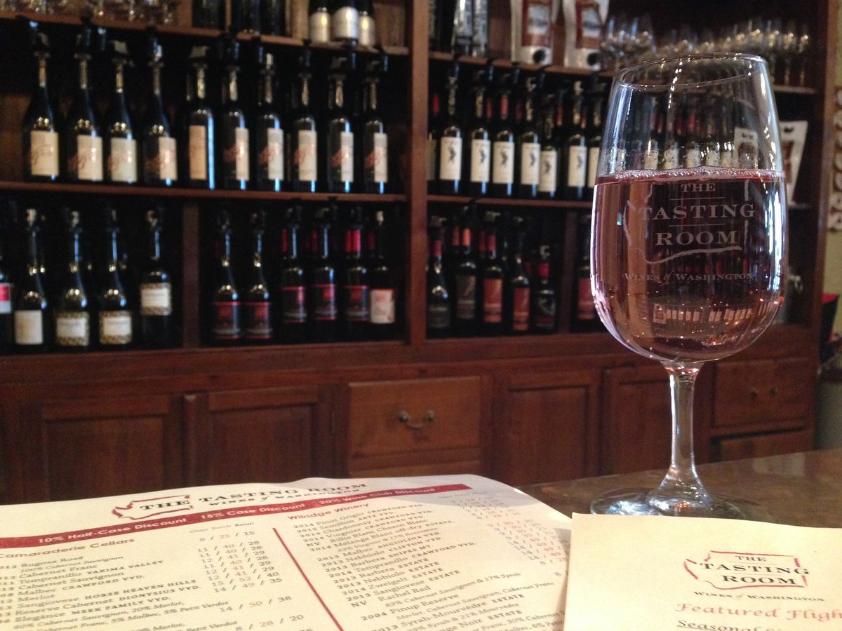 A glass of pink-hued wine at The Tasting Room with shelves of bottles in the background.