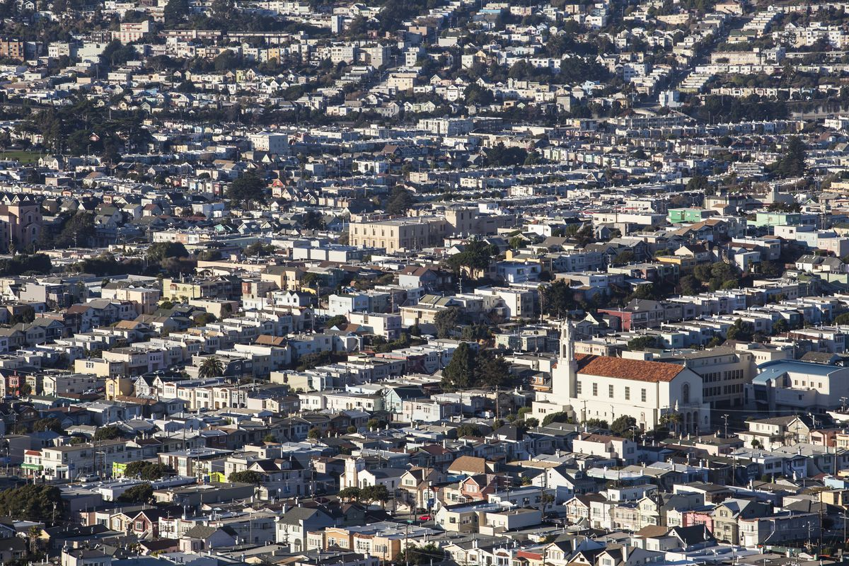 An aerial photo of thousands of San Francisco homuses with a church prominently in the foreground.