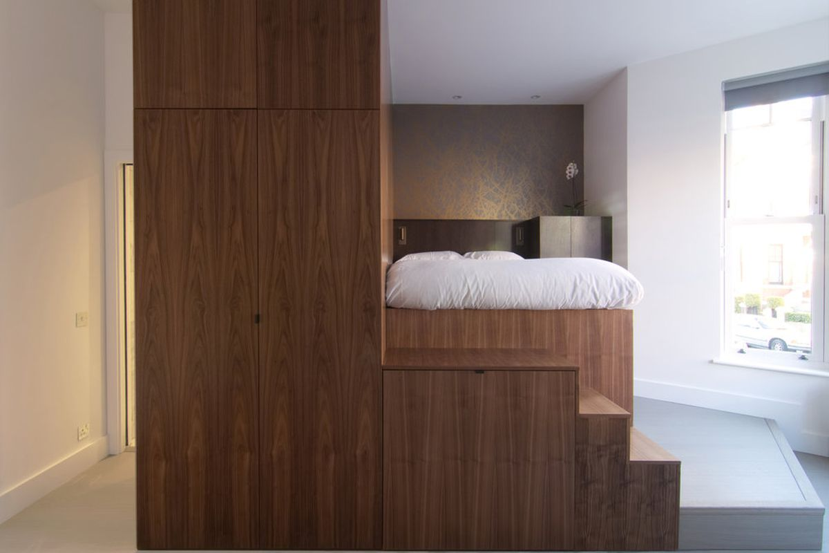 Wooden unit in center of small studio apartment comprising close, steps up to a platform bed, and a kitchen.