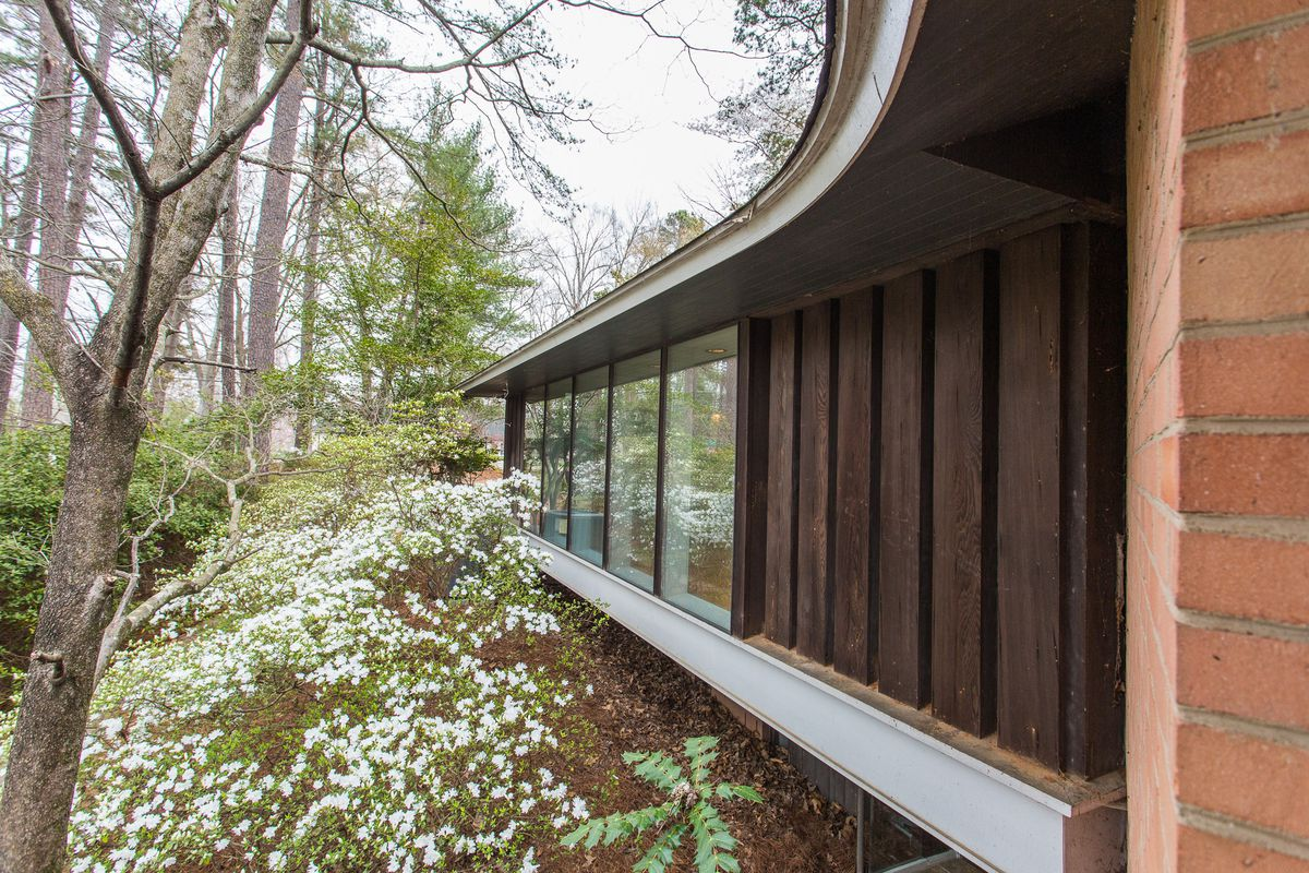 An exterior view of the home with glass panels, a curving roofline, and a forest.