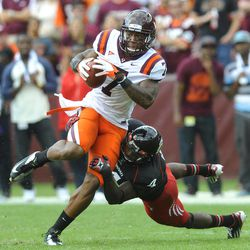 Virginia Tech's Marcus Davis (7) tries to get away from Cincinnati's Maalik Bomar (4) after he caught a pass for a first down during the first half of an NCAA college football game, Saturday, Sept. 29, 2012, in Landover, Md.