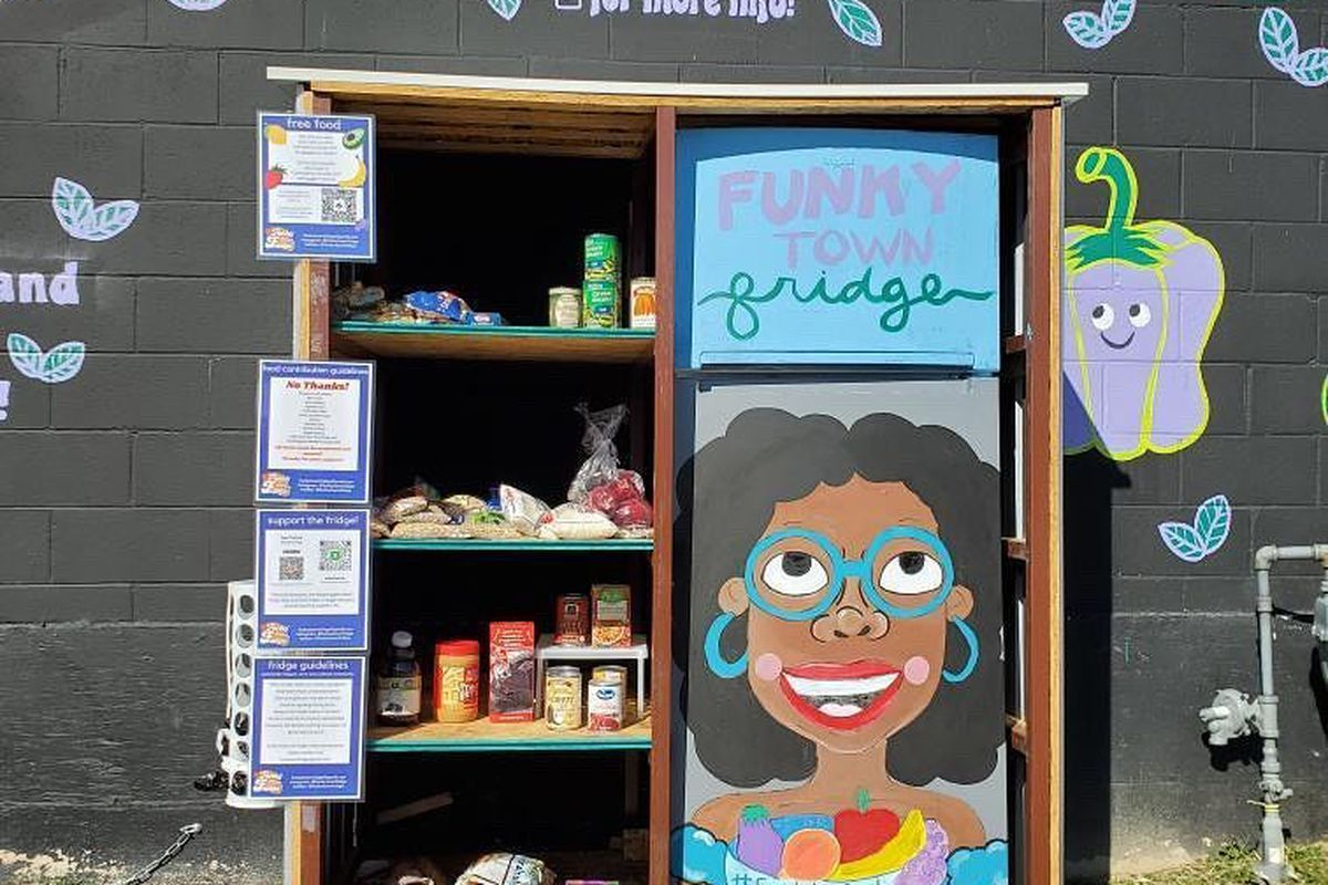 community fridge featuring a hand-painted mural of a girl with black hair and blue hoop earrings holding a bowl of fruit