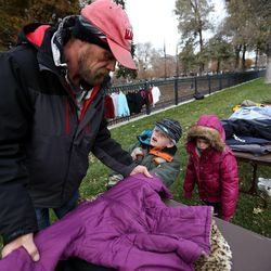 Fred Rivers looks for coats with Todd Jr. Dickerman and Lakota Beal at the 10th annual Community Coat Exchange at Pioneer Park in Salt Lake City on Friday, Nov. 28, 2014.